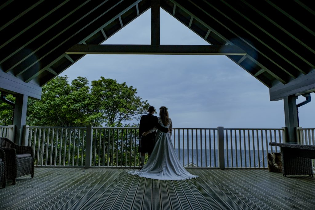 bride and groom at boat house wedding